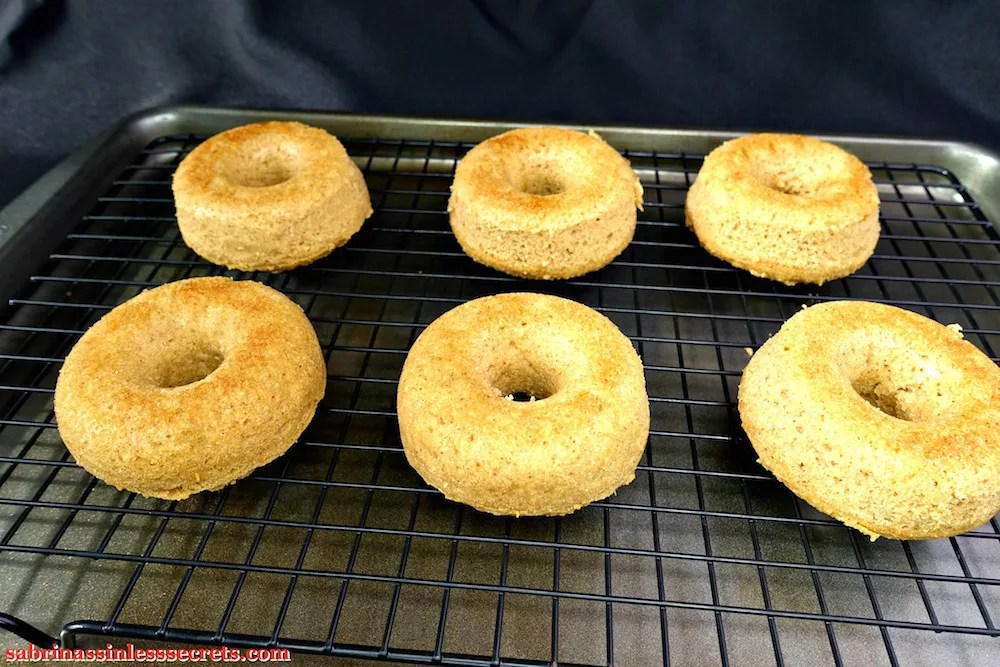 Paleo Maple Glazed Baked Donuts fresh out of the oven on a cooling rack with a cookie sheet underneath it on a black background