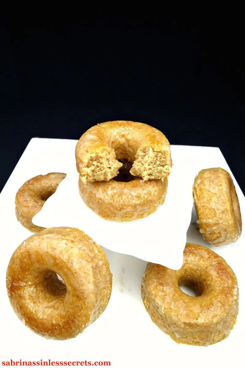 A stack of Paleo Maple Glazed Baked Donuts, the top one bitten in half, on a white square serving platter with more circling them on a white marble slab