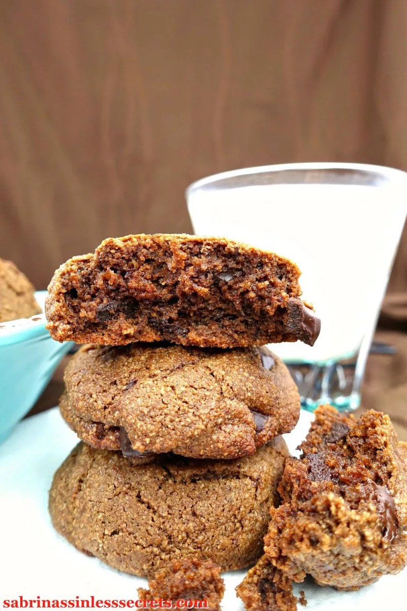 A stack of three Double Dark Chocolate Chunk Paleo Brownie Cookies, the top one broken in half with the other half against the bottom of the stack, on a white plate with a glass of almond milk in the background