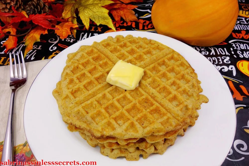 Pumpkin waffles on a white plate with pat of butter