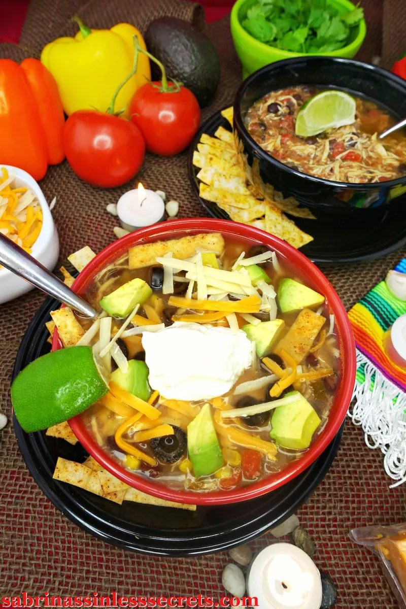 A bowl of the gluten free chicken tortilla soup with a variety of toppings