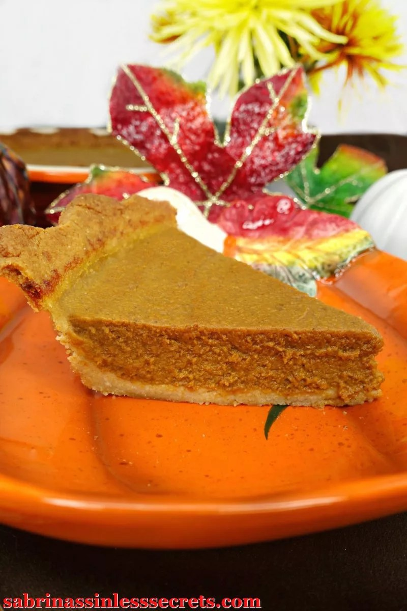 Paleo pumpkin pie slice sits on top of a festive fall plate with flowers in the background