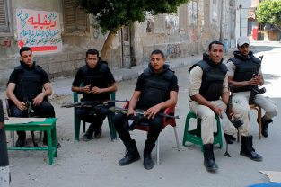 Egyptian security forces take a break as they prepare to watch the area in Beni Sueif.