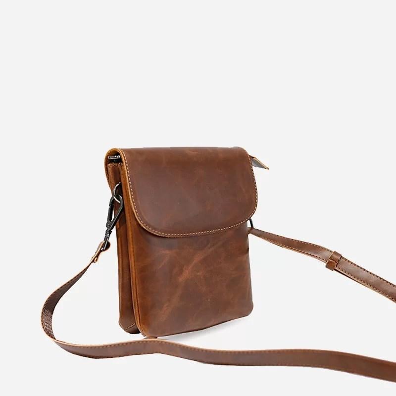 Petit sac besace reporter pour homme en cuir marron avec sa bandoulière.