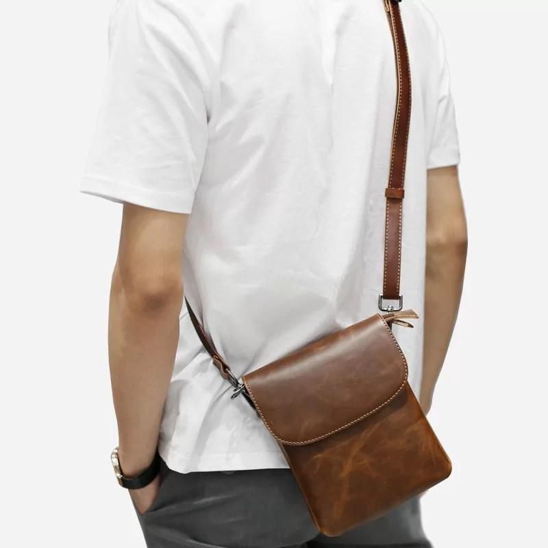Sacoche besace reporter pour homme en cuir marron avec sa bandoulière porté épaule.