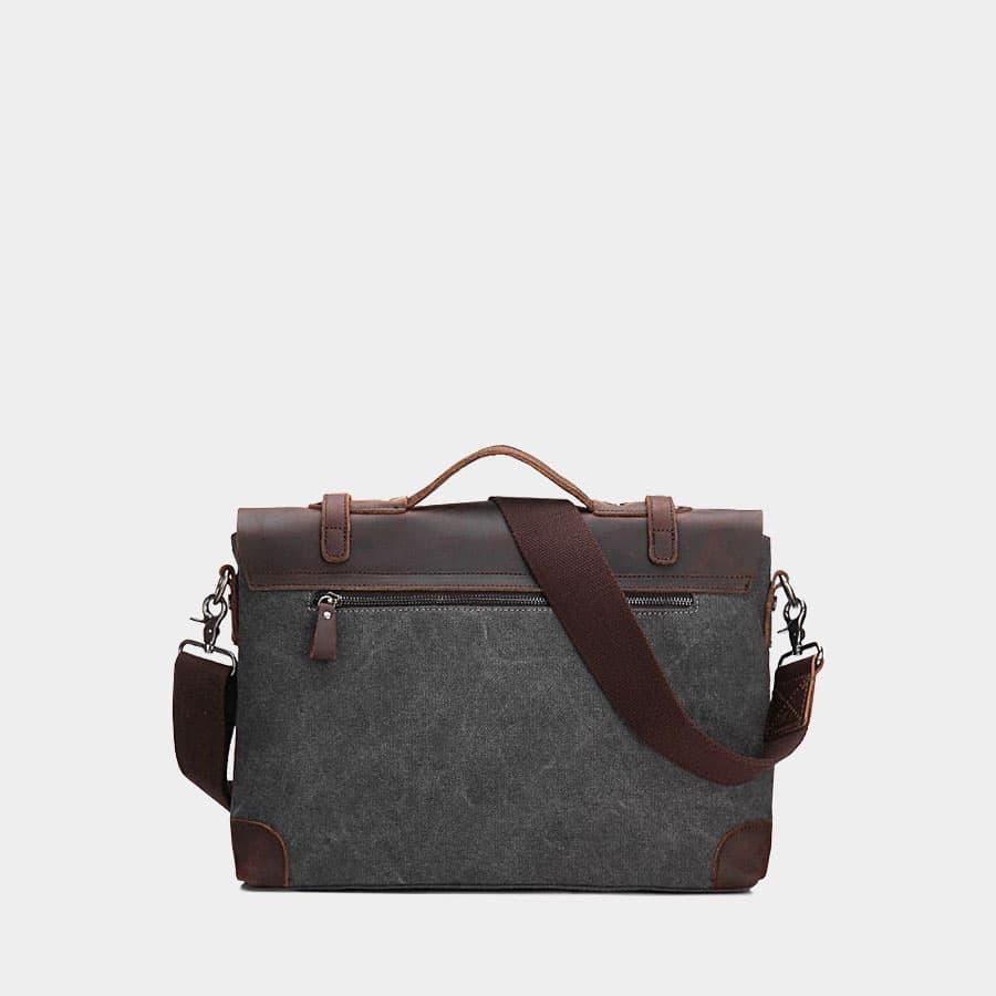 Verso de la sacoche besace en toile noire et cuir véritable brun foncé.