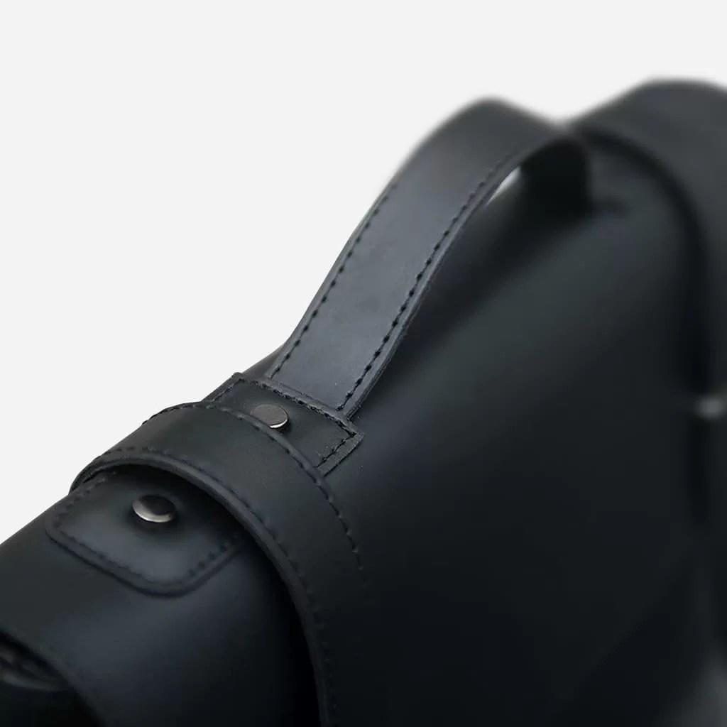 Zoom anse et bride à boucle de la sacoche besace bandoulière en cuir noir pour homme.