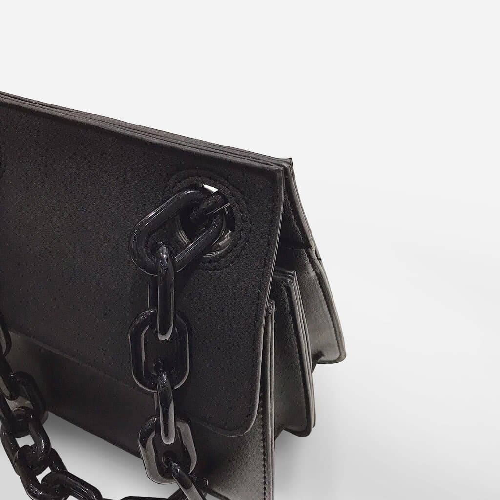 Détail des maillons de la grosse chaîne noire en métal du sac besace.
