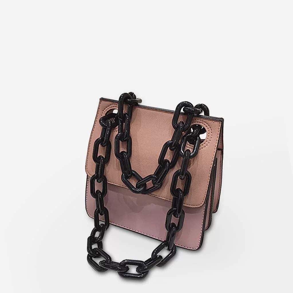Sac besace bandoulière rose à chaîne noire.