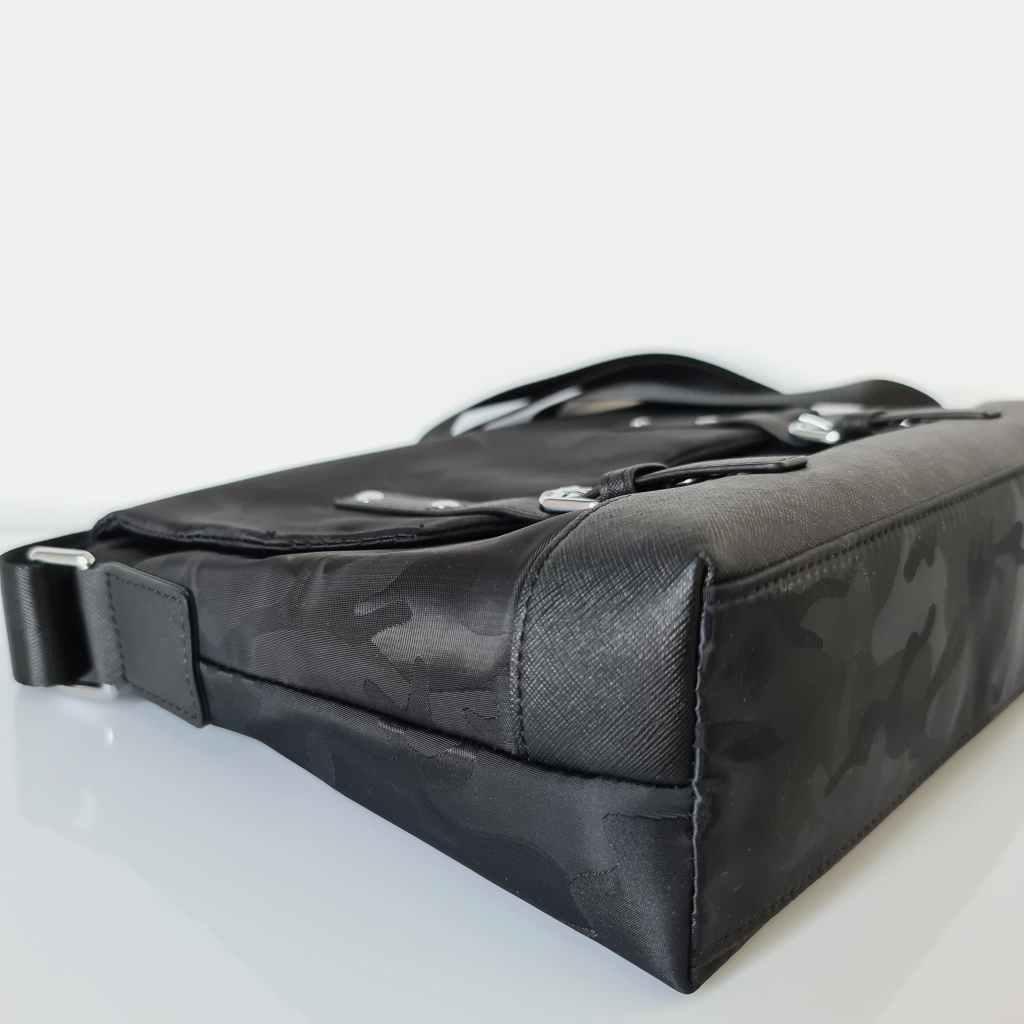 Dessous du sac besace homme noir avec excellentes finitions en tissu Oxford camouflage et cuir safiano.