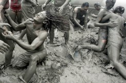 Tourists play with the mud during the 15th annual mud festival on Daecheon Beach in Boryeong, South Korea, Sunrday, July 15, 2012. The festival features mud wrestling, mud sliding and mud king contest. (AP Photo/Ahn Young-joon)