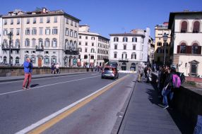 Crossing over the Arno River, John takes a photo-op traffic risk!