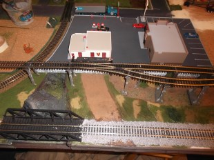 I started to ballast the track. This was hard on the nerves. I will wait until it dries, try it out and if everything is good, I will finish the track. You can also see the backside of the DQ and gas station.