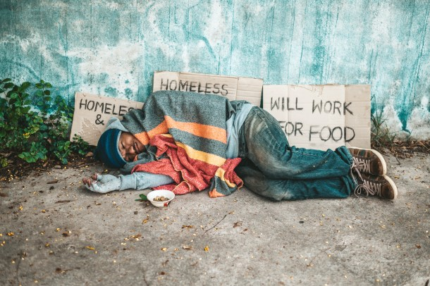 The beggars lay on their side of the street with dirty clothes.