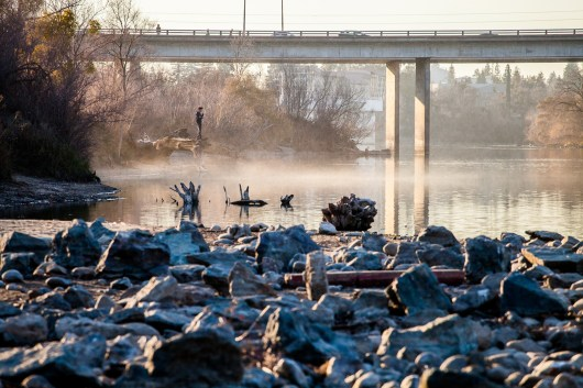 An onlooker observes low water levels of the American River at the Howe Avenue River Access point.