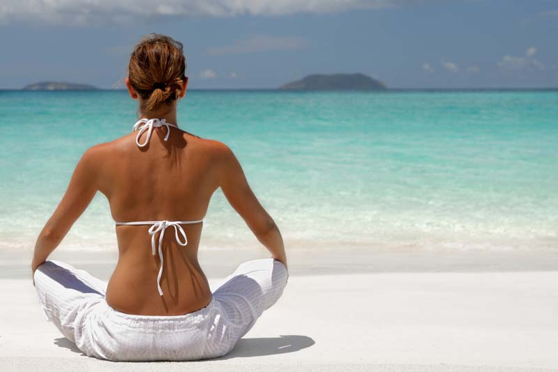 woman meditating on tropical beach in the caribbean