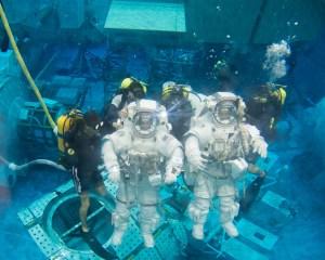 SCUBA divers assisting astronauts underwater