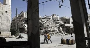 أطفال سوريون يسيرون أمام مبنى مدمر في طريقهم إلى المدرسة بمحافظة إدلب - يونسيف
