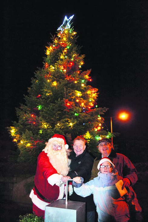 Father Christmas, Mike Sweeney, Gilbert Symes and Emma Shaw light up the tree in Delph