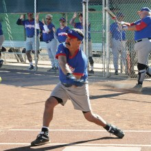 Tom Klein takes a mighty swing while Jim Smith warms up; photo by Ron Finelli.