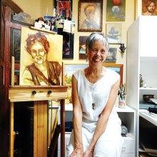 Karen Warner pauses in her studio with an in-progress portrait.