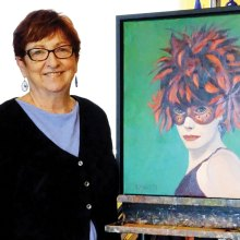 Sandy Merritt poses in her studio with Boa Head, one of her favorite portraits.