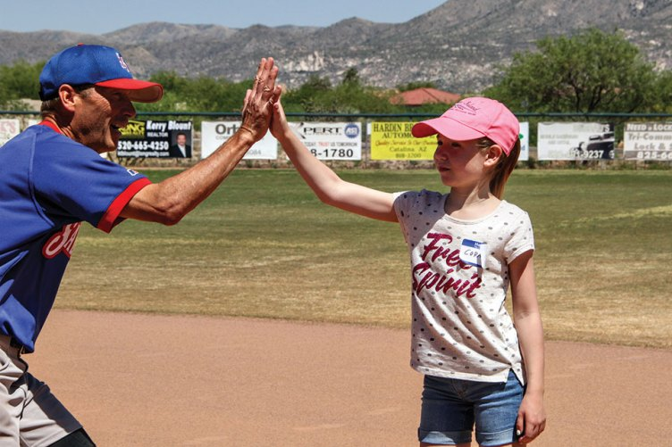 Cora gets a high five from Coach Jeff Stolze; photo by Jim Smith.