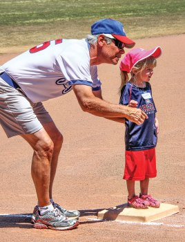 Quinn is ready to run home from third base with encouragement from Grandpa/Coach Terry Mihora; photo by Jim Smith.