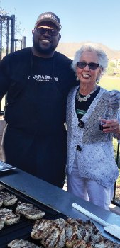 Jeff Berry, Carrabba's, and Bonnie Barazani, social chairman for The Preserve, grin while teasing the crowd with the tantalizing aroma of almost ready Chicken Marsala.