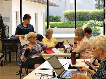The ladies put down their knitting needles and listen intently to Linda Hood as she explains use of the knitting website, Ravelry.