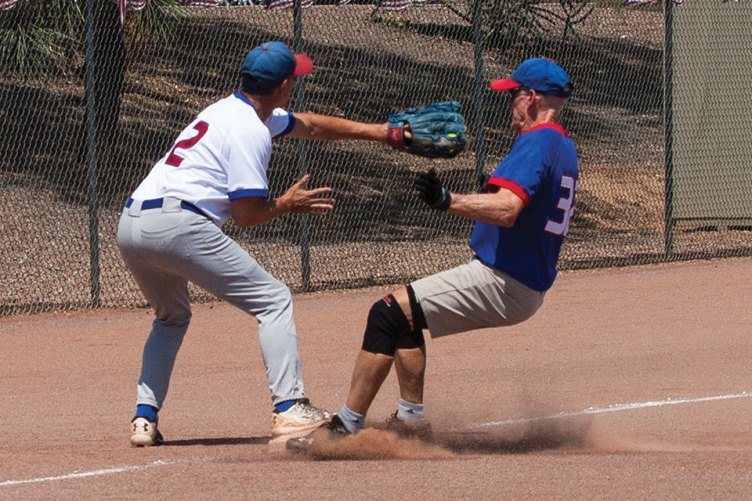 Competitive: Harold Weinenger reaches to tag runner Don Jones as he stirs up the dust at third base; photo by Dennis Purcell