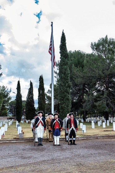 Sons of the American Revolution standing under the flag