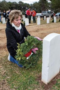 Linda Nicholson of SaddleBrooke Ranch laying wreath at veteran's grave