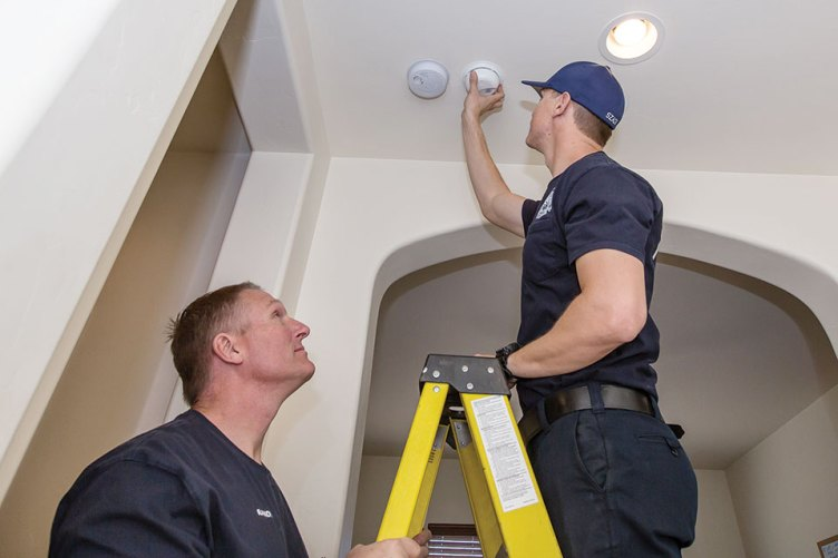 Ryan Szach, fire Fighter/EMT, on a ladder about to replace batteries in a smoke detector while Randy Schulzkump, engineer/EMT, holds the ladder; Photo by Steve Weiss