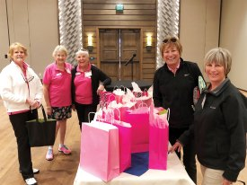 Raffle prizes surrounded by several members of the Putters' event committee (left to right): Anne Terrell, Irene Kiel (event chairman), Linda Zoellner, Corky Mansmith and Debbie Norwood.