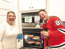 Hosts Jan Storey and Jon Swanson, ready to bring more pans of homemade lasagna to the buffet; photo by Camille Esterman