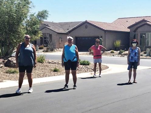 D. Fitzgerald, Doris Carlin, Corky Mansmith, and Linda Newton practice social distancing on a walk.