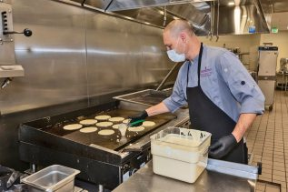 Jeremy Immes, Director of food and beverage, making pancakes for the event. (Photo by Steve Weiss)
