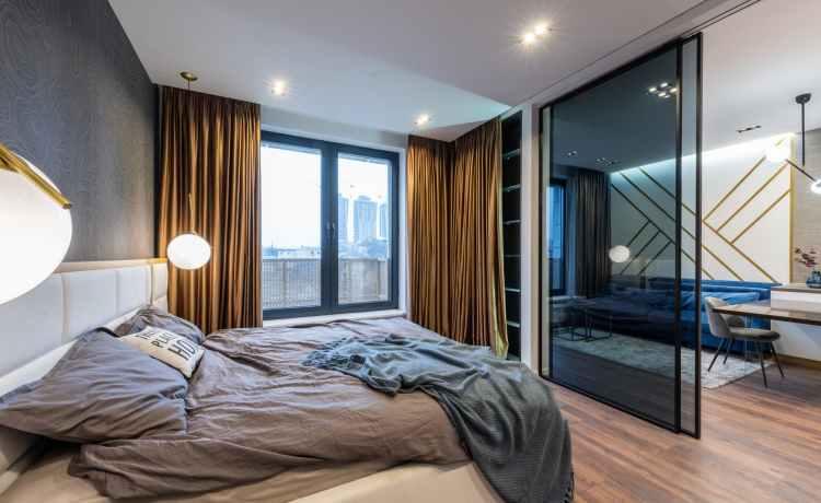 bedroom interior with unmade bed near glass door and window