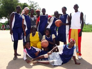 Some of the ladies line up to take photographs following the basketball tournament.