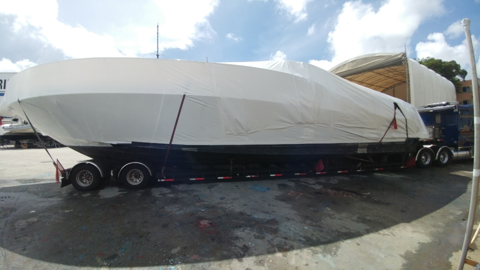 Full length picture of the Sundancer from the left side. It is fully shrink wrapped and secured to the trailer.
