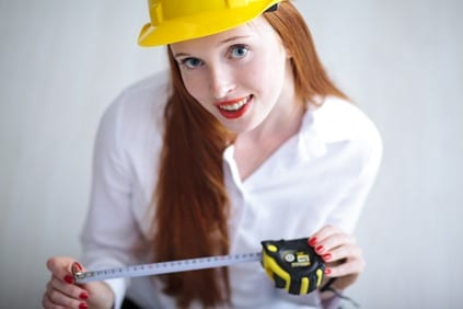 Young beautiful female with yellow helmet holding a tape measure