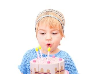 Pretty little girl blowing on candles in the cake