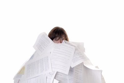 businesswoman drowning in a mountain of papers
