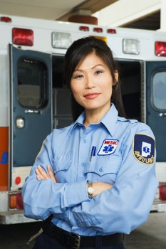 Asian female paramedic smiling in front of ambulance