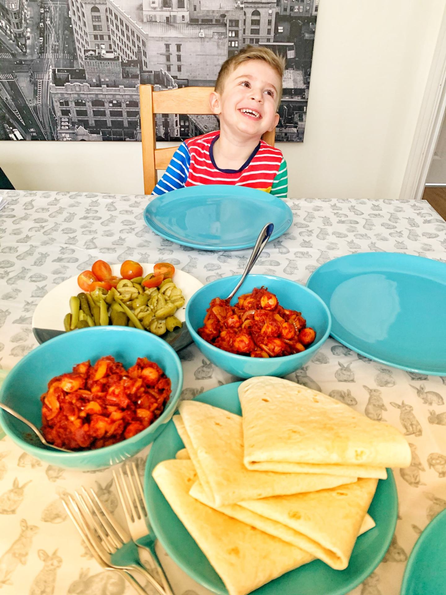 Toddler with sosis Bandari in front of him on dining table