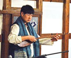 宗教儀式で使われたとされる3本弦のタンブールを紹介する北川修一さん=有田町の手塚商店