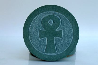 Egyptian motive on green round stone