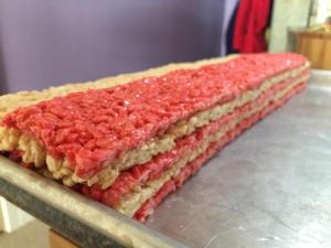 Alternating thin layers of red and white rice krispie treat are stacked up to resemble the stripes of the American Flag