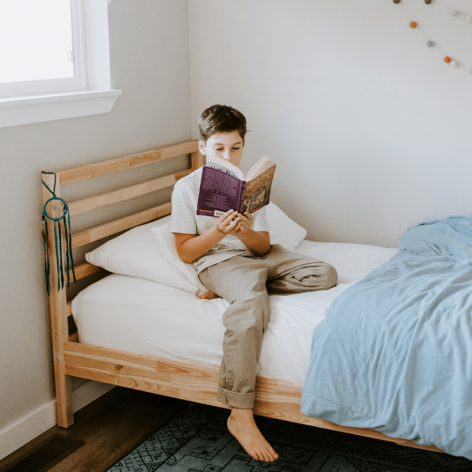 Homeschooled boy reading Harry Potter on a bed in a minimalist kids bedroom.